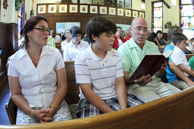 (L-r) Maria Lund, her son Ethen, her husband Eric and their other children join the congregation in singing the offertory hymn during the final Sunday liturgy at the Cantonment Chapel. Eric is active duty military and a base physician. His family is relocating to Fort Bragg, North Carolina.  (Page 11, June 23, 2011 issue)