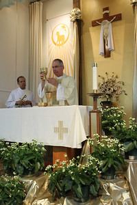 Father Fred Wendel elevates the chalice during the consecration of the final Sunday Mass. Joining him at the altar is Deacon Peter Swan of St. Philip Benizi Church, Jonesboro. Deacon Swan, an intelligence information services officer at Fort McPherson, was the homilist for the June 5 Mass.