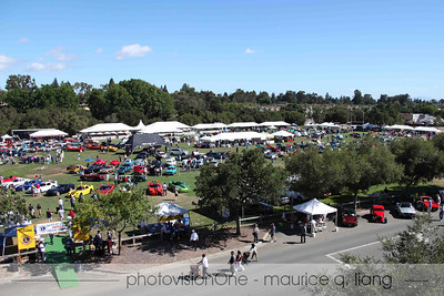 Birds eye view of the concours.  300+ cars on the field.  Cars for sale in foreground.