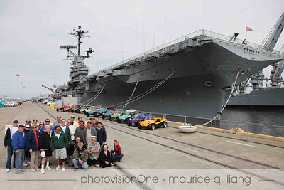 Group poses in front of the USS Hornet.