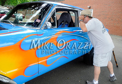 6/18/2011 Mike Orazzi | Staff Rob Marola lifts his sunglasses while peering inside of a 1961 Ford Falcon during the Klingberg Vintage Motor Car Festival at the Klingberg campus on Linwood Street in New Britain on Saturday.