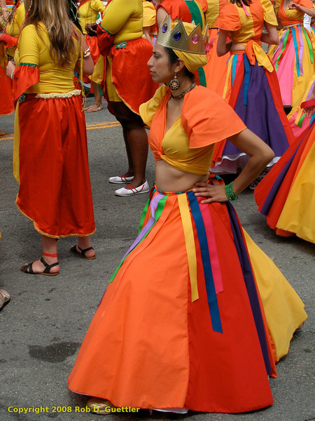 Dancing group in bright red and orange. Brasil Cuba-SF (?), Carnaval Parade 2008 staging. Bryant St. near 24th St., Mission District, San Francisco, California.