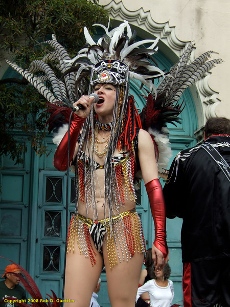 Costumed singer on float with headdress. MaraReggae, Carnaval Parade 2008 staging. Bryant St. near 24th St., Mission District, San Francisco, California.