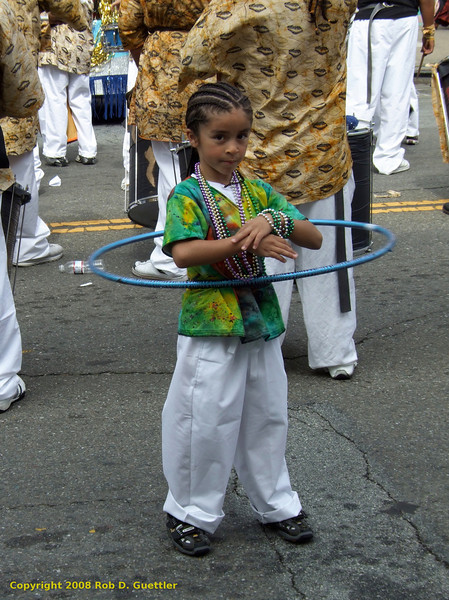 Child marching with hula-hoop. Loco Bloco, Mission Girls & Leonard Flynn Elementary School; Carnaval Parade 2008 staging. Bryant St. near 24th St., Mission District, San Francisco, California.