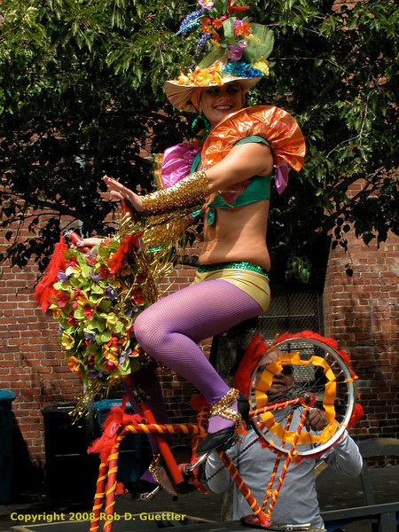 Colorful bicyclist riding stationary bicycle on bike-powered float. Cyclecide, Carnaval Parade 2008 staging. Bryant St. near 24th St., Mission District, San Francisco, California.