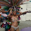 Dancer placing feather headset. Aquarela Brazilian Dance, Carnaval Parade 2008 staging. Bryant St. near 24th St., Mission District, San Francisco, California.