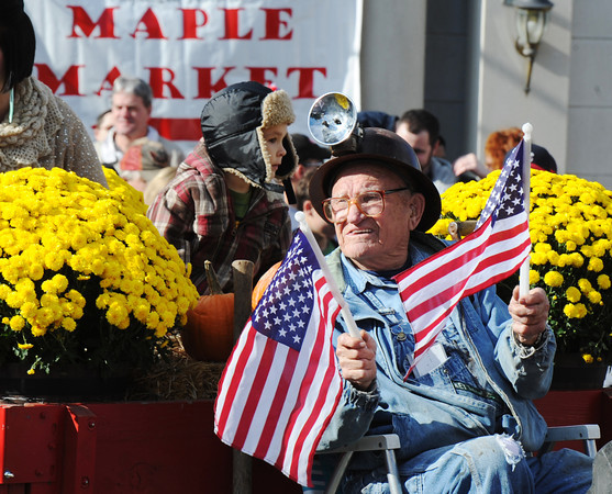 A participant wears a miners helmet and waves US flags from a float during the Maple Leaf Parade Saturday morning, Oct. 19, 2013.<br /> Globe | T. Rob Brown