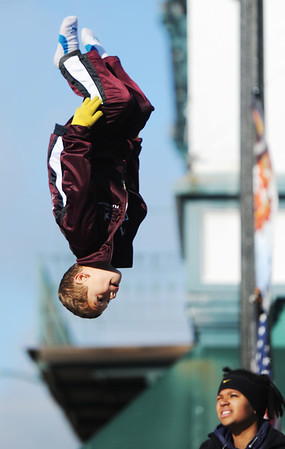 A participant on the Flip Shop's trampoline float goes heels-over-head during the Maple Leaf Parade Saturday morning, Oct. 19, 2013, on the Carthage Square.<br /> Globe | T. Rob Brown