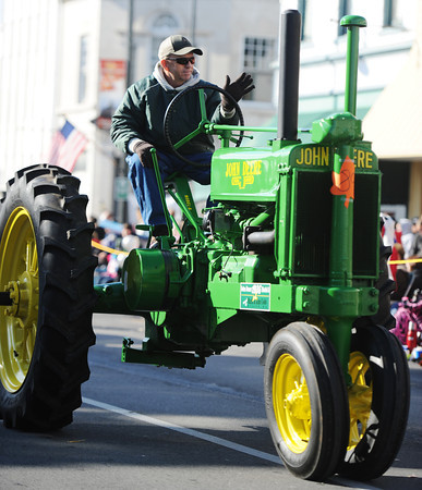 A 1936 John Deere Model A tractor owned by Mark and Kim Cobb of Miller travels down the Carthage Square during the Maple Leaf Parade Saturday morning, Oct. 19, 2013.<br /> Globe | T. Rob Brown