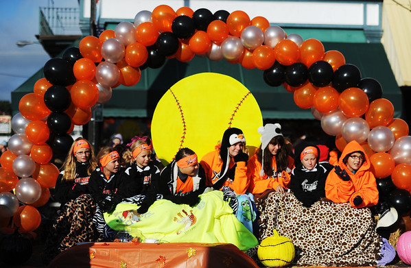 Softball players smile and wave from the Xtreme Fastpitch float during the Maple Leaf Parade Saturday morning, Oct. 19, 2013, on the Carthage Square.<br /> Globe | T. Rob Brown