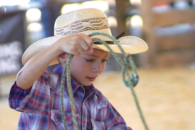 Matthew Gaston | The Sheridan Press <br /> Shaw Moore, 7, works on get his rope untangled after an uncooprative goat twisted it up during the Cates Goat Roping event at the Sheridan County Fairgrounds Saturday, Sept. 12, 2020.