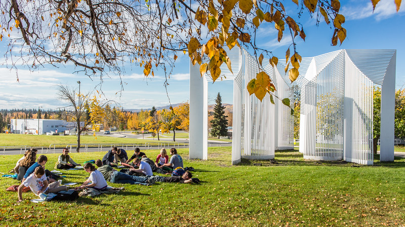 A German foreign language class holds class on the campus lawn during a warm autumn afternoon.