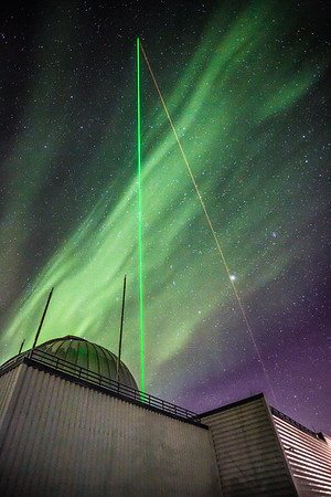 A lidar beam, a combination of radar and a laser, shines approximately 50 miles straight up into the night sky through a bright aurora from a building at UAF's Poker Flat Research Range. The beam measures high altitude temperatures in conjunction with a planned rocket launch.