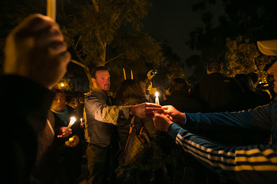 Attendees pass out candles outside Balboa Park's House of France, Thursday, January 8, 2015, at a vigil for the victims of the Charlie Hebdo attack in Paris.