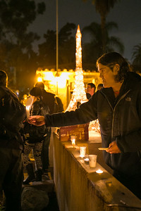 Kirk Edwards passes out candles outside Balboa Park's House of France, Thursday, January 8, 2015, at a vigil for the victims of the Charlie Hebdo attack in Paris.