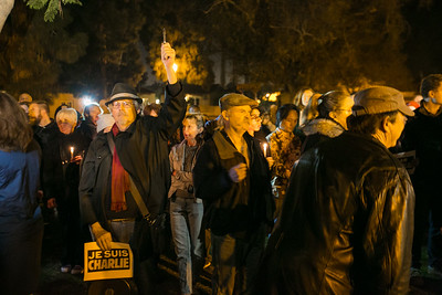Attendees hold pencils, pens and candles outside Balboa Park's House of France, Thursday, January 8, 2015, at a vigil for the victims of the Charlie Hebdo attack in Paris.