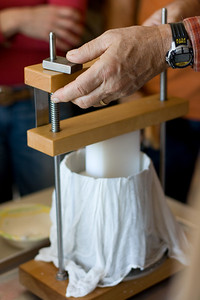 This is the loaded cheddar press.  The cheese is wrapped in cheesecloth.  A metal plate at the top is pressed down and this presses the liquid out of the cheese.