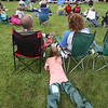 Chelm of sford Community Band performs concert on Town Common in its Summer on the Common series. Neve Lambert, 9, of Chelmsford, with parents Gavin and Becky Lambert, was a little cold so she put the covers of the folding chairs on her legs. (SUN/Julia Malakie)