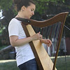 Saturday Farmers Market on Chelmsford Town Common. Harpist Anna Portillo of Chelmsford, who writes her own songs, and also books, performs at Farmers Market. (SUN/Julia Malakie)