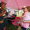 Saturday Farmers Market on Chelmsford Town Common. Divya JOhnson of Chelmsford, left, director for Thirty-one Gifts, which sells bags, totes and home organizing items, show an example to Melissa Moore of Chelmsford and her daughter Sophia, 13 months old. (SUN/Julia Malakie)