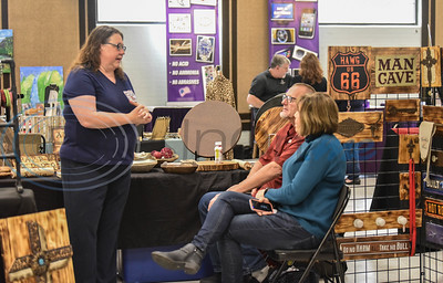 Event organizer Kim Felt (left) speaks with vendors at her Cherokee Craft & Trade Fair on Saturday, March 14. The event took place at the Ruby Ballroom in Jacksonville.