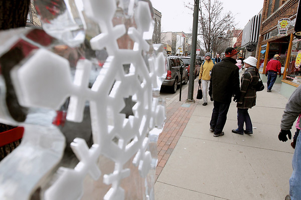 Record-Eagle/Keith King<br /> Pedestrians walk downtown near an ice sculpture Saturday, February 19, 2011 during the Cherry Capital Winter Wow!Fest.