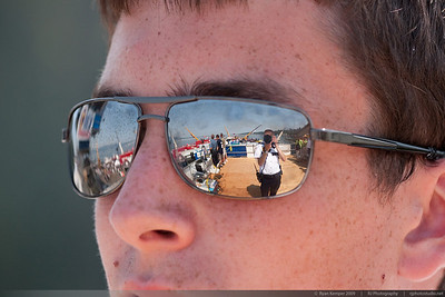 A Seattle Police Explorer watches the Blue Angels perform Sunday afternoon from his post atop the media tower. A panoramic view of the hydroplane pits can be seen in the reflection of his sunglasses.
