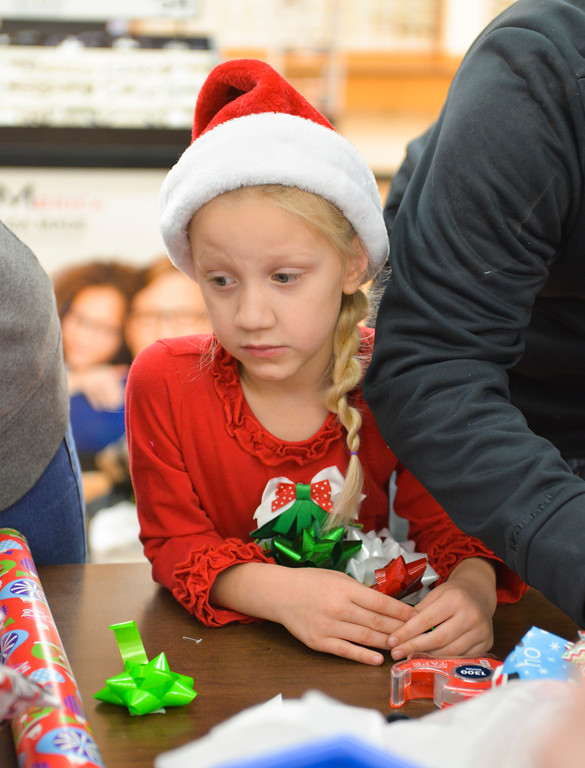 "Justin Sheely | The Sheridan Press	<br /> Lucky Seven 4-H club volunteer Finnley Koltiska, 6, looks on as gifts are wrapped during ""Shop with a Cop"" at Walmart Saturday, Dec. 9, 2017. Walmart donated $2000 to the Shop with a Cop program, which helps children buy holiday gifts for their families."