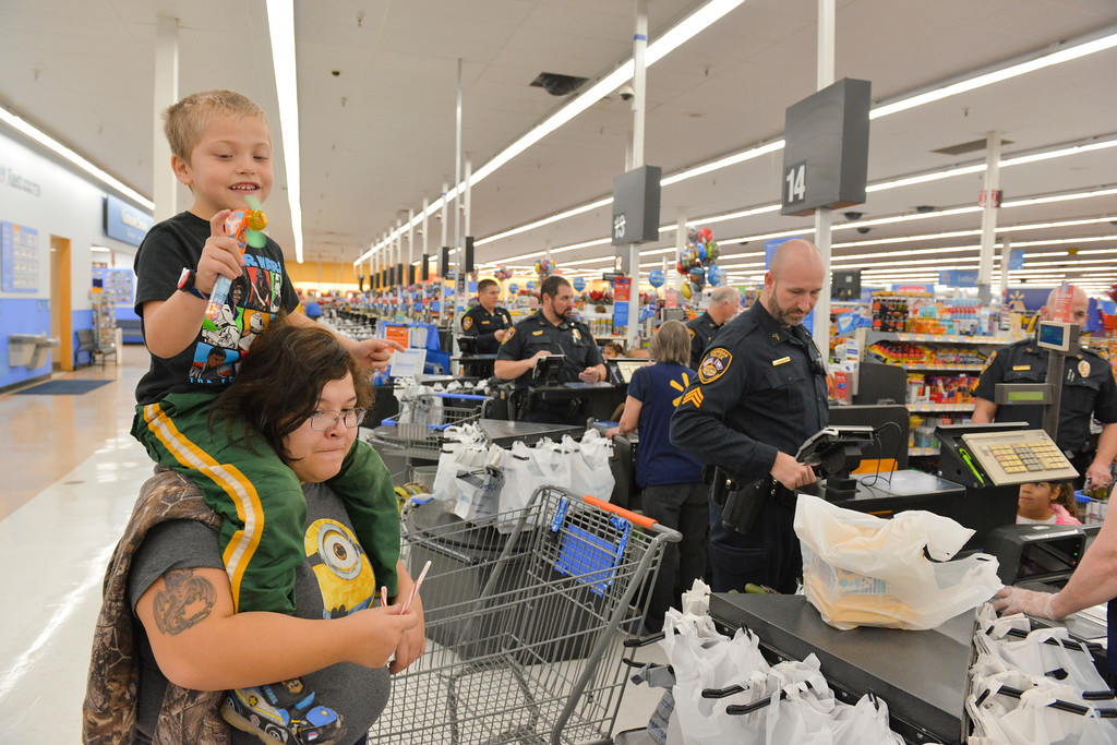"Justin Sheely | The Sheridan Press	<br /> Eighteen-year-old Ayla Williams holds her brither Jonathan Williams as a Sheridan Police officer purchases their gifts during ""Shop with a Cop"" at Walmart Saturday, Dec. 9, 2017. Walmart donated $2000 to the Shop with a Cop program, which helps children buy holiday gifts for their families."