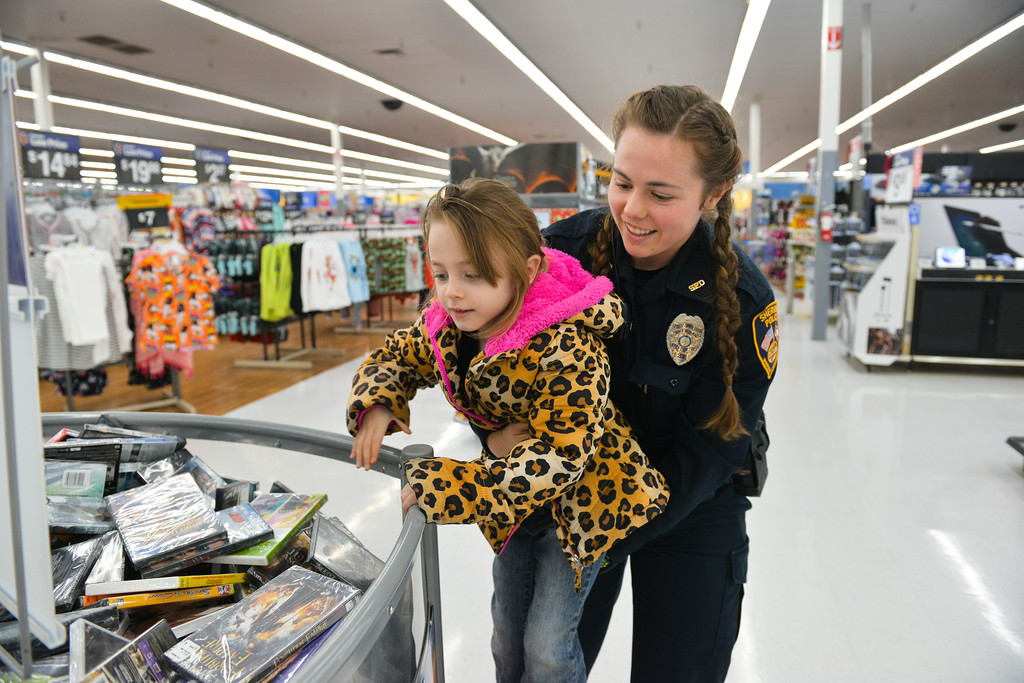 "Justin Sheely | The Sheridan Press	<br /> Sheridan Police officer Meagan Phillips helps Laney Keefe, 5, look through movies during ""Shop with a Cop"" at Walmart Saturday, Dec. 9, 2017. Walmart donated $2000 to the Shop with a Cop program, which helps children buy holiday gifts for their families."