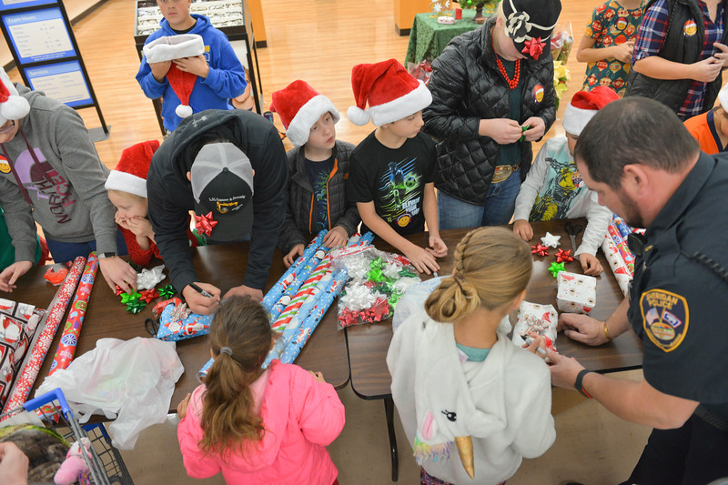 "Justin Sheely | The Sheridan Press	<br /> Lucky Seven 4-H club volunteers handle the gift wrapping during ""Shop with a Cop"" at Walmart Saturday, Dec. 9, 2017. Walmart donated $2000 to the Shop with a Cop program, which helps children buy holiday gifts for their families."