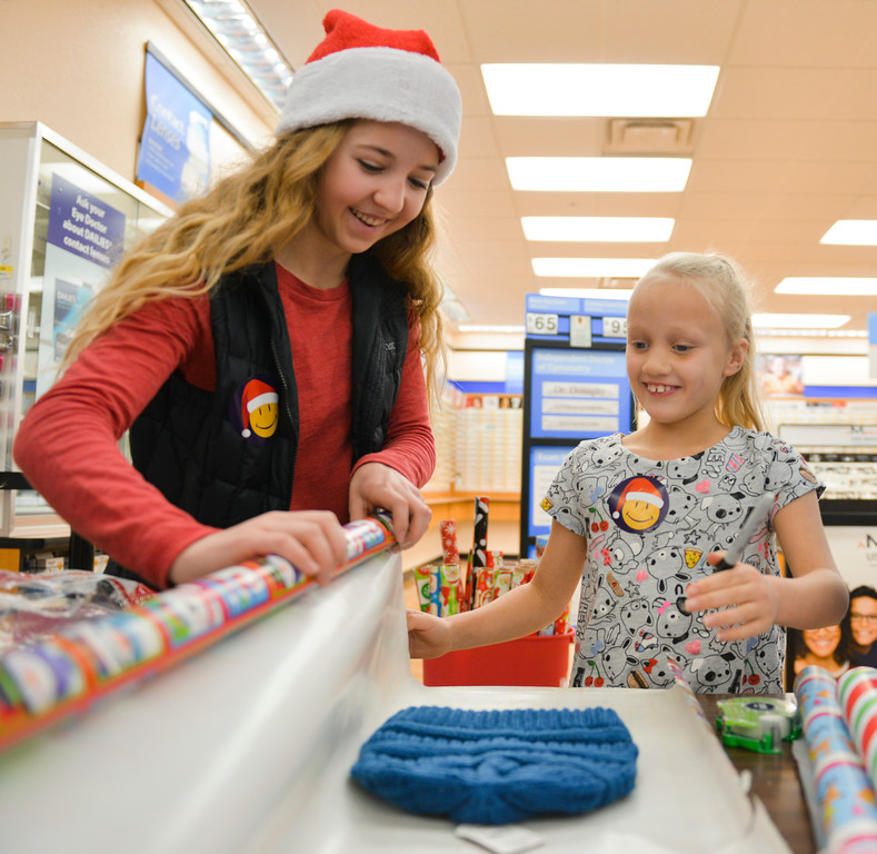 "Justin Sheely | The Sheridan Press	<br /> Lucky Seven 4-H club volunteers Olivia Chase, 15, left, and Juniper Koltiska gift wrap during ""Shop with a Cop"" at Walmart Saturday, Dec. 9, 2017. Walmart donated $2000 to the Shop with a Cop program, which helps children buy holiday gifts for their families."
