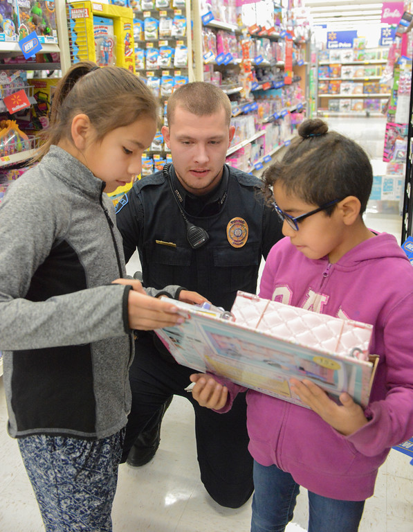"Justin Sheely | The Sheridan Press	<br /> Northern Wyoming Community College District officer Brayden Dempsey watches as Dancing Lite Old Man, 9, left, and Manuela Addison, 8, look at a toy during ""Shop with a Cop"" at Walmart Saturday, Dec. 9, 2017. Walmart donated $2000 to the Shop with a Cop program, which helps children buy holiday gifts for their families."