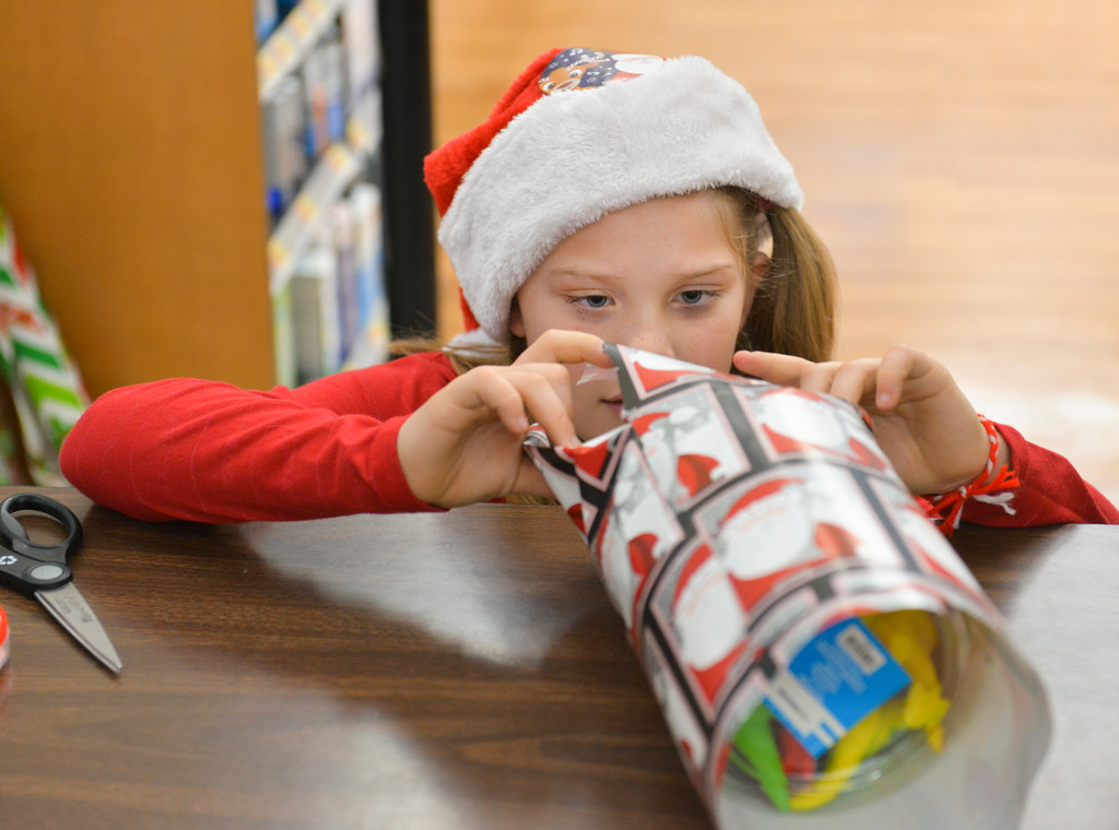 "Justin Sheely | The Sheridan Press	<br /> Lucky Seven 4-H club member Willow Koltiska, 9, volunteers as a gift wrapper during ""Shop with a Cop"" at Walmart Saturday, Dec. 9, 2017. Walmart donated $2000 to the Shop with a Cop program, which helps children buy holiday gifts for their families."