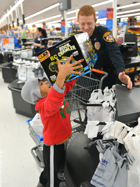 "Justin Sheely | The Sheridan Press	<br /> Five-year-old Luis Cortes picks up his gift as Sheridan Police officer Devereaux Johnson purchases the gifts during ""Shop with a Cop"" at Walmart Saturday, Dec. 9, 2017. Walmart donated $2000 to the Shop with a Cop program, which helps children buy holiday gifts for their families."