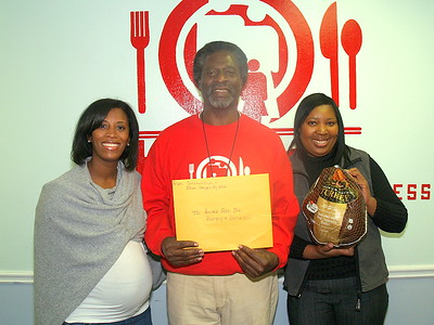 """Monique Evans, (L) President & Founder of The Children's Pride Foundation and Tonya Drummer, (R) Children's Pride Program Coordinator and Owner of The Signature Planner presenting Actor, Afemo Omilami, Co-Director of """"Hosea Feed The Hungry and Homeless"""" with a montery donation, turkeys and can goods."""