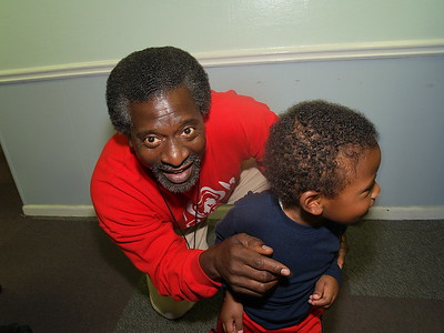 """Actor, Afemo Omilami, Co-Director of """"Hosea Feed The Hungry and Homeless"""" plays with Ethan, son of Monique Evans, President & Founder of The Children's Pride Foundation and Ben Evans of Photo Images By Ben."""