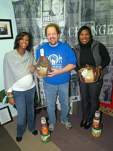 """Monique Evans, (L) President & Founder of The Children's Pride Foundation and Tonya Drummer, (R) Children's Pride Program Coordinator and Owner of The Signature Planner presenting a volunteer of """"Hosea Feed The Hungry and Homeless"""" with turkeys and can goods."""