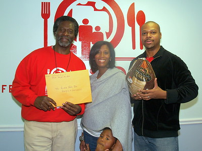 """Monique Evans, (C) President & Founder of The Children's Pride Foundation and Ben Evans, (R) of Photo Images By Ben with their son presenting Actor, Afemo Omilami, Co-Director of """"Hosea Feed The Hungry and Homeless"""" with a montery donation, turkeys and can goods."""