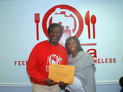 """Monique Evans, President & Founder of The Children's Pride Foundation presenting  Actor, Afemo Omilami, Co-Director of """"Hosea Feed The Hungry and Homeless"""" with a montery donation, turkeys and can goods."""