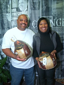 """Richard (L) and Tonya Drummer, (R) Children's Pride Program Coordinator and Owner of The Signature Planner presenting """"Hosea Feed The Hungry and Homeless"""" with turkeys and can goods."""
