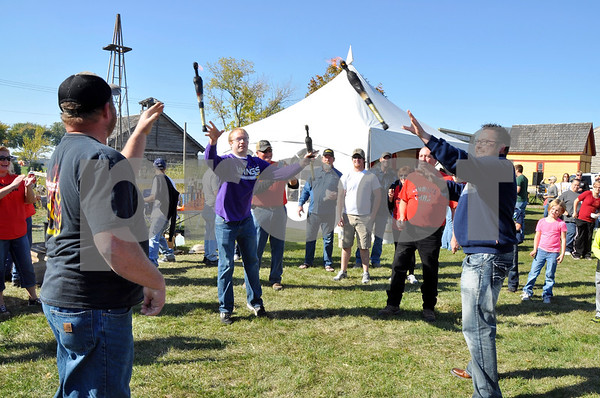-Messenger photo by Joe Sutter<br /> <br /> Robert Barton, left, Alex Moore and Ken Busby toss flaming batons around in a circle after volunteering to be part of Chuck Reetz's skit, at right in red shirt. Reetz said he usually juggles the flaming batons himself, but he had audience members do it this time instead.