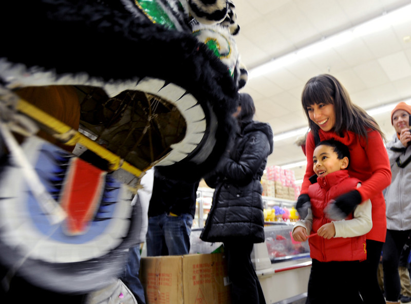 """Alexandra Schroeder and her son, Jaiden, get to see the lions up close inside the marketplace.<br /> Members of the Tai Kung Ha Holistic Fitness Center performed a Chinese New Year Lion Dance at Pacific Ocean II Marketplace in Broomfield on Saturday.<br /> For more photos and a video, go to  <a href=""""http://www.dailycamera.com"""">http://www.dailycamera.com</a>.<br /> Cliff Grassmick / February10, 2013"""