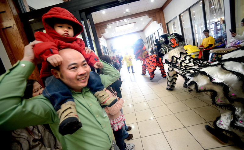 """Bryant Nguyen holds up his son, Benjamin, 2, so he can see the lion dance.<br /> Members of the Tai Kung Ha Holistic Fitness Center performed a Chinese New Year Lion Dance at Pacific Ocean II Marketplace in Broomfield on Saturday.<br /> For more photos and a video, go to  <a href=""""http://www.dailycamera.com"""">http://www.dailycamera.com</a>.<br /> Cliff Grassmick / February10, 2013"""