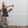 Young woman prepares to hang Merry Chriatmas decoration in apartment.