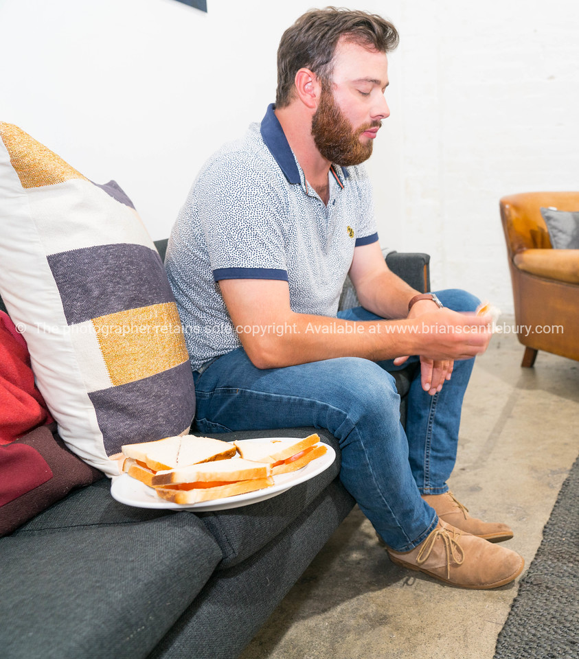 Bearded man sitting on couch eating sandwich with plate beside him.