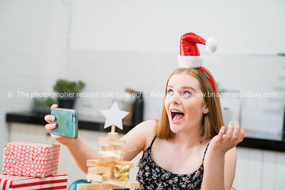 Young woman at table with presents and decorations taking selfie on Christmas morning.