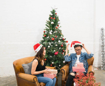 Young Asian couple under Christmas tree
