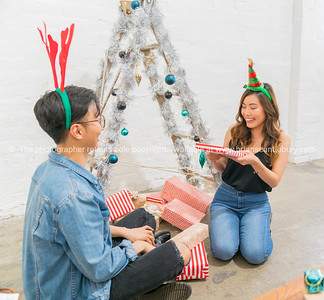 Young Asian couple under ladder tree together on Christmas morning.