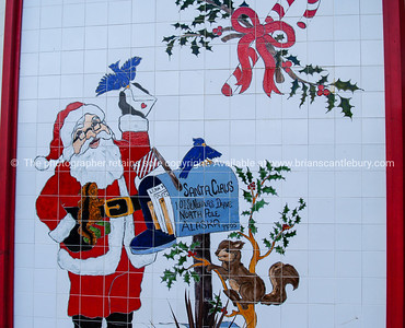 White tiled wall with image of Santa Claus alonside his letter box.